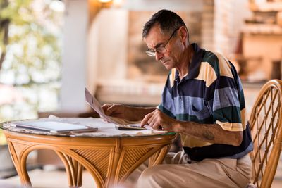 Senior citizen man seriously evaluating paperwork at a home table