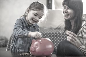 Girl inserting coin from mother into red piggy bank on coffee table