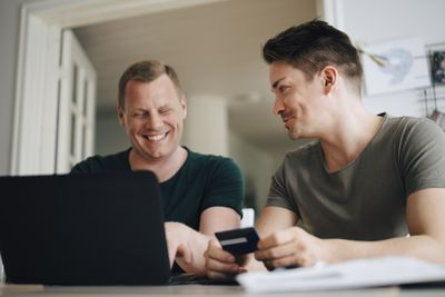 Smiling couple paying bill through laptop on dining table at home