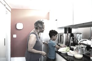 An older woman supervises a child washing produce in a sink in a tidy kitchen.