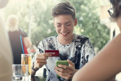 Smiling young man holding credit card and mobile phone.