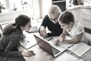 Woman sits at table with two younger girls, focused on a laptop computer.