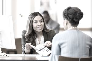 An employee in business attire shows an information brochure to a customer.