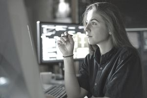 A young woman with long hair is seated at a desk and looking at a monitor.