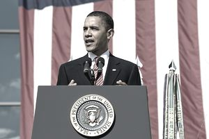 President Barack Obama speaking at an event backed by a large American flag
