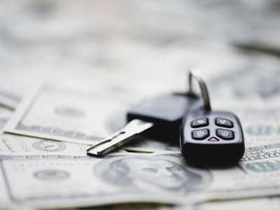 car keys laying on top of currency