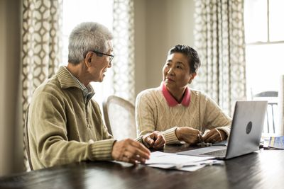 Senior couple using laptop with paperwork at home