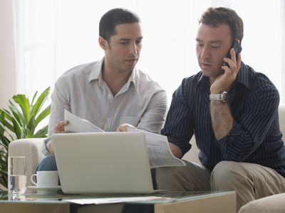 A couple sit on their couch, reviewing their bills while talking on the phone to a debt collector