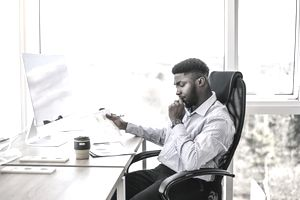 Successful businessman working on paperwork at computer in his office. Reusable coffee cup on the table.
