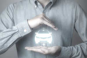 Person holding a graphic of a car representing gap car insurance