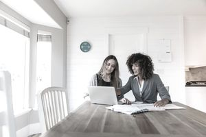 Woman with Straight Blond Hair and Second Woman with Curly Brown Hair Sit at a Kitchen Table Working on Taxes on a Laptop