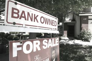 """A """"For Sale"""" sign with a notice of it being bank owned in front of a house."""