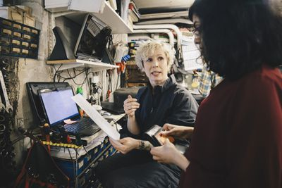 Female mechanic showing receipt to customer with credit card