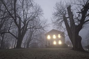 spooky house at night surrounded by trees