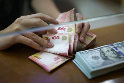 A teller counts Indonesian 100,000 rupiah banknotes with a stack of U.S. one-hundred dollar banknotes laying nearby.