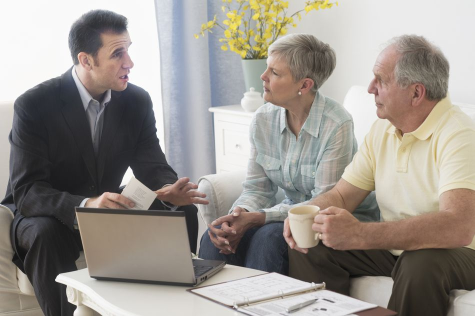 Senior couple talking to businessman in living room