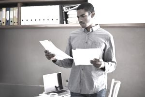 Shot of a handsome young businessman looking over some paperwork in his home office