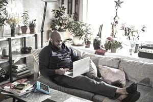 man uses credit card with laptop on sofa