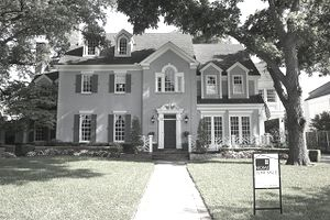 A stately gray house with a for sale sign out front