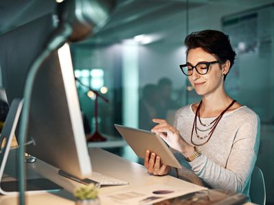 Woman wearing spectacles working on tablet sitting in front of monitor in an office