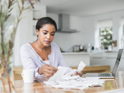 A woman reviewing her credit card bills at her kitchen table