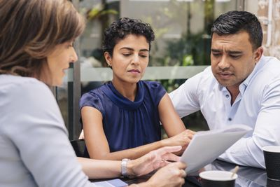 A couple looks over paperwork with a lender representative