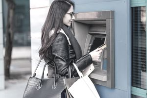 A young woman accessing her bank account with an ATM