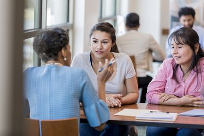 Bank advisor having a discussion with two young women at a desk