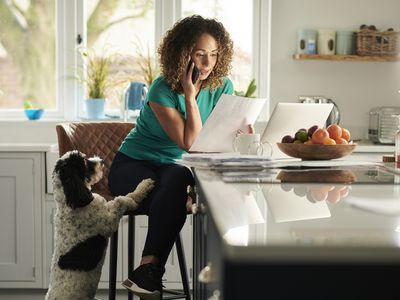 A woman talks on the phone while working from home in her kitchen. Her dog stands beside her, looking for attention