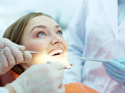 Person Having Teeth Checked While Smiling at Orthodontist