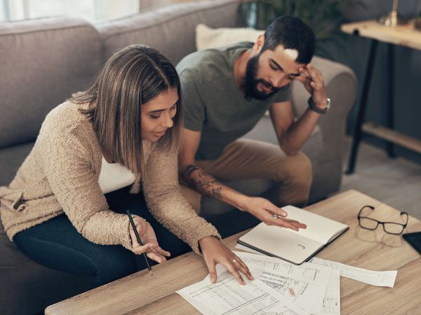 young couple reviews a pile of bills on a coffee table.