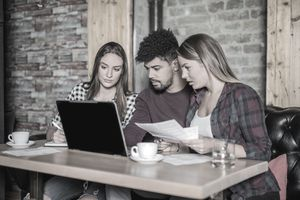 Two Young Women and One Young Man at Laptop in Coffee Shop, Looking at Screen and Holding Paperwork