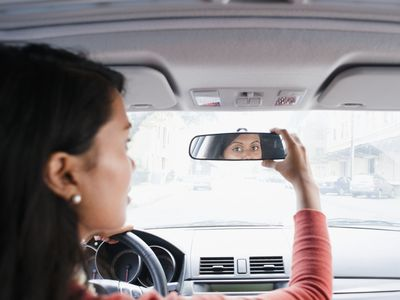 Woman looking at review mirror in car