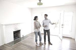 Realtor and woman standing in an empty, bright room as he shows the house