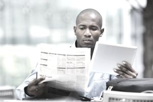 Man holding tablet and looking at the stock page in a newspaper