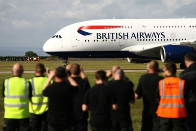 British Airways plane taxis on an airport runway.