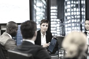 Female manager sitting at the head of the table at a company meeting and speaking seriously.