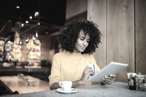 A woman sits a table in a quiet cafe and considers getting a credit limit increase.