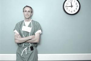 Doctor standing in front of a healthcare Clock