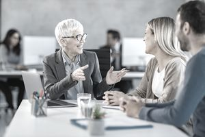 Mature female banker talking to couple in a meeting in an office