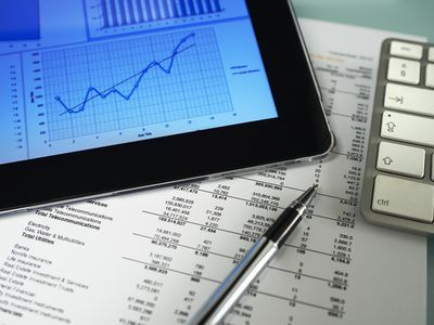 stock market chart on tablet with pen, paper, calculator