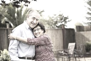 Elderly spouses smiling and hugging in a back yard