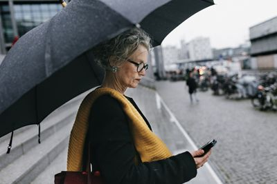 Woman with a black umbrella looking at her phone