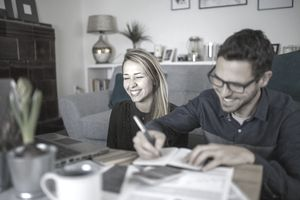 Laughing couple recording expenses in a notebook
