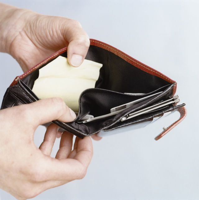 person holding open the empty currency compartment of a wallet