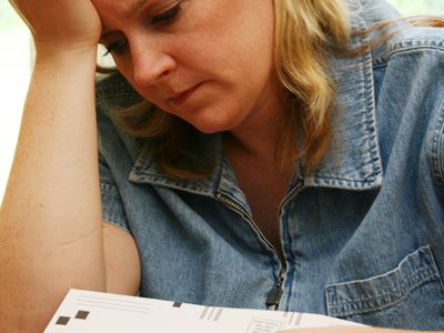 White woman with head resting on hand looking at past due bills.