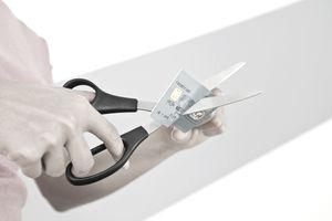 Person cutting up a credit card with a large pair of scissors