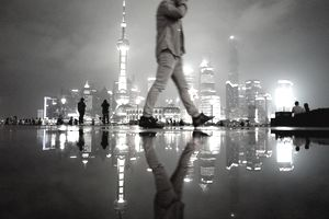 Man walking down the street on a rainy night in Shanghai.