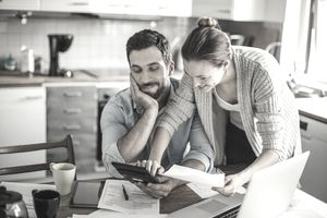Couple in kitchen paying bills
