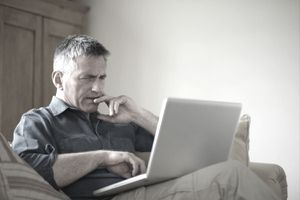 Worried man on a sofa frowning at his laptop